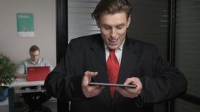 Hombre de negocios acertado joven en el traje que juega en una tableta, usando una tableta El hombre trabaja en un ordenador en e almacen de video