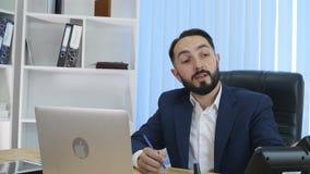 Hombre de negocios acertado joven que habla en el teléfono, fondo de la oficina metrajes