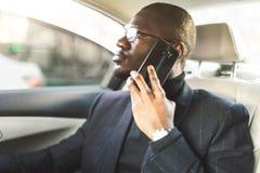 Hombre de negocios acertado joven que habla en el tel?fono que se sienta en el asiento trasero de un coche costoso Negociaciones  foto de archivo libre de regalías