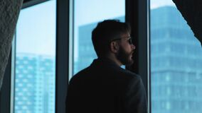 Hombre de negocios acertado joven que mira hacia fuera la ventana el centro de la ciudad Alto edificio del asunto Oficina en esti almacen de metraje de vídeo