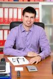 Hombre de negocios acertado joven que trabaja en su escritorio Fotos de archivo libres de regalías