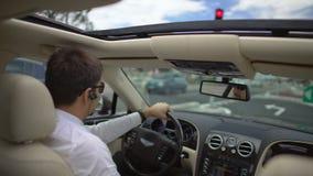 Hombre de negocios acertado que conduce el coche costoso para trabajar a toda prisa, transporte almacen de video