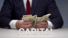Hombre de negocios acertado que cuenta el capital corporativo de las manos almacen de metraje de vídeo