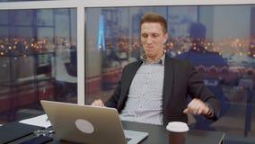 Hombre de negocios acertado que disfruta de buenas noticias del correo electrónico en lugar de trabajo de la oficina almacen de video