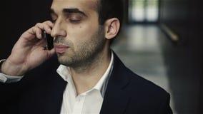 Hombre de negocios acertado que habla en su teléfono celular metrajes