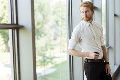 Hombre de negocios acertado que hace una pausa la ventana Imagen de archivo libre de regalías