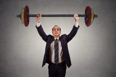 Hombre de negocios acertado que levanta sin esfuerzo el barbell pesado imagen de archivo libre de regalías
