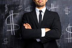 Hombre de negocios acertado que presenta delante de muestras de dólar Imagen de archivo libre de regalías