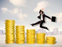 Hombre de negocios acertado que salta para arriba en el dinero de la moneda de oro Imágenes de archivo libres de regalías