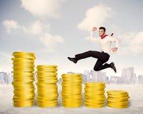Hombre de negocios acertado que salta para arriba en el dinero de la moneda de oro Fotografía de archivo libre de regalías