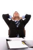 Hombre de negocios acertado que se relaja sobre su escritorio foto de archivo libre de regalías