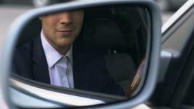 Hombre de negocios acertado que se sienta en coche y que mira en el espejo de la vista lateral, conductor almacen de metraje de vídeo