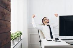 Hombre de negocios acertado que se sienta en su oficina fotos de archivo libres de regalías