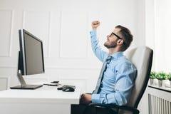 Hombre de negocios acertado que se sienta en su oficina fotografía de archivo