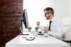 Hombre de negocios acertado que se sienta en su oficina imagen de archivo
