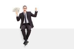 Hombre de negocios acertado que se sienta en un panel en blanco Imágenes de archivo libres de regalías