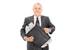 Hombre de negocios acertado que sostiene la cartera llena de dinero Foto de archivo libre de regalías