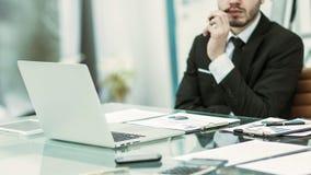 Hombre de negocios acertado que trabaja con los documentos financieros en el escritorio Imagenes de archivo