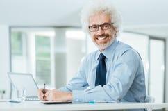 Hombre de negocios acertado que trabaja en el escritorio de oficina Fotos de archivo libres de regalías