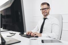 Hombre de negocios acertado que trabaja en su oficina imagen de archivo libre de regalías