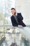 Hombre de negocios acertado sonriente en llamada de teléfono móvil Fotografía de archivo libre de regalías