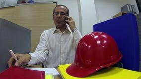 Hombre de negocios acertado Talking en el teléfono móvil en la oficina