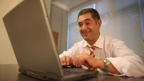 Hombre de negocios acertado usando el ordenador portátil en oficina almacen de metraje de vídeo