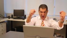 Hombre de negocios acertado usando el ordenador portátil en oficina almacen de video