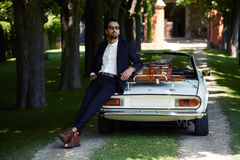 Hombre de negocios acertado y rico que disfruta de un día durante viaje en el coche de lujo del cabriolé en el camino del campo Imagen de archivo libre de regalías