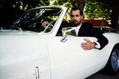 Hombre de negocios acertado y rico que se sienta detrás de la rueda de su coche de lujo del cabriolé en el camino del campo Foto de archivo libre de regalías