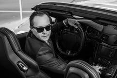 Hombre de negocios acertado de yang en coche amarillo del cabrio imagen de archivo libre de regalías