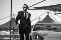 Hombre de negocios acertado de yang en coche amarillo del cabrio fotos de archivo