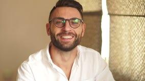 Hombre de negocios activo en las sonrisas blancas de la camisa y de los vidrios ampliamente mientras que mira en la cámara Retrat almacen de video