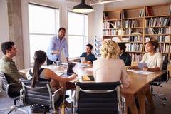 Hombre de negocios Addressing Team Meeting Around Table Fotos de archivo