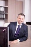 Hombre de negocios adulto atractivo en su escritorio en oficina Imagenes de archivo