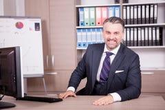 Hombre de negocios adulto atractivo en su escritorio en oficina Fotografía de archivo libre de regalías