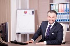 Hombre de negocios adulto atractivo en su escritorio en oficina Imágenes de archivo libres de regalías