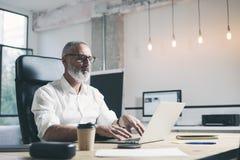 Hombre de negocios adulto atractivo y positivo usando el ordenador portátil móvil mientras que trabaja en la tabla de madera en m Imagenes de archivo