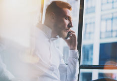 Hombre de negocios adulto barbudo de la foto que trabaja en oficina moderna del desván Sirva la camisa blanca que lleva y usar sm Imágenes de archivo libres de regalías