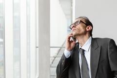 Hombre de negocios adulto de las lentes que habla en el teléfono Fotografía de archivo libre de regalías