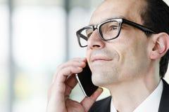 Hombre de negocios adulto de las lentes que habla en el teléfono Fotos de archivo