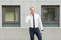 Hombre de negocios adulto joven que llama su jefe, mirando la cámara y la sonrisa Imagen de archivo
