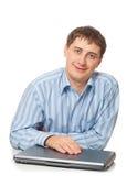 Hombre de negocios adulto joven que se sienta con la computadora portátil cerrada Imagenes de archivo