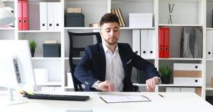 Hombre de negocios adulto joven que viene en lugar de trabajo en oficina moderna almacen de video