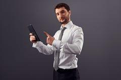 Hombre de negocios adulto joven que señala en la PC de la tableta Foto de archivo libre de regalías
