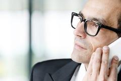 Hombre de negocios adulto que sueña despierto que habla en el teléfono Imagenes de archivo