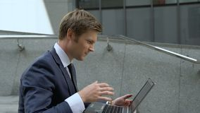 Hombre de negocios afortunado usando el ordenador portátil para comprobar el mercado de acción, sentándose en las escaleras al ai almacen de video