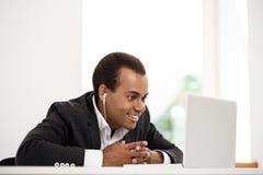Hombre de negocios africano acertado joven en los auriculares sonrisa, mirando el ordenador portátil Imagen de archivo