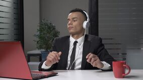 Hombre de negocios africano acertado joven en traje que escucha la música en el ordenador en los auriculares, bailando en la ofic metrajes