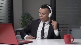 Hombre de negocios africano acertado joven en traje que escucha la música en el ordenador en los auriculares, bailando en la ofic almacen de metraje de vídeo